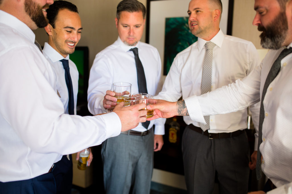 groomsmen cheers with whiskey before wedding