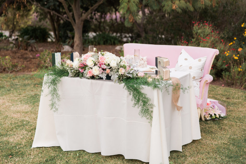 Sweetheart table with pink chair and books at garden wedding