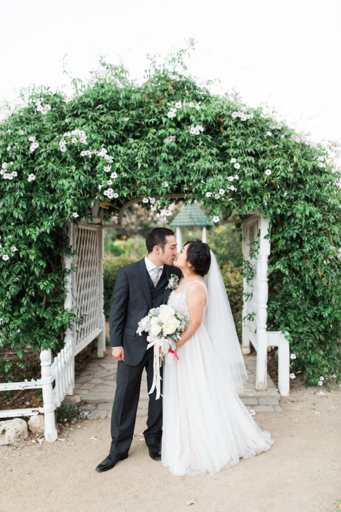 bride and groom in garden under greenery arch