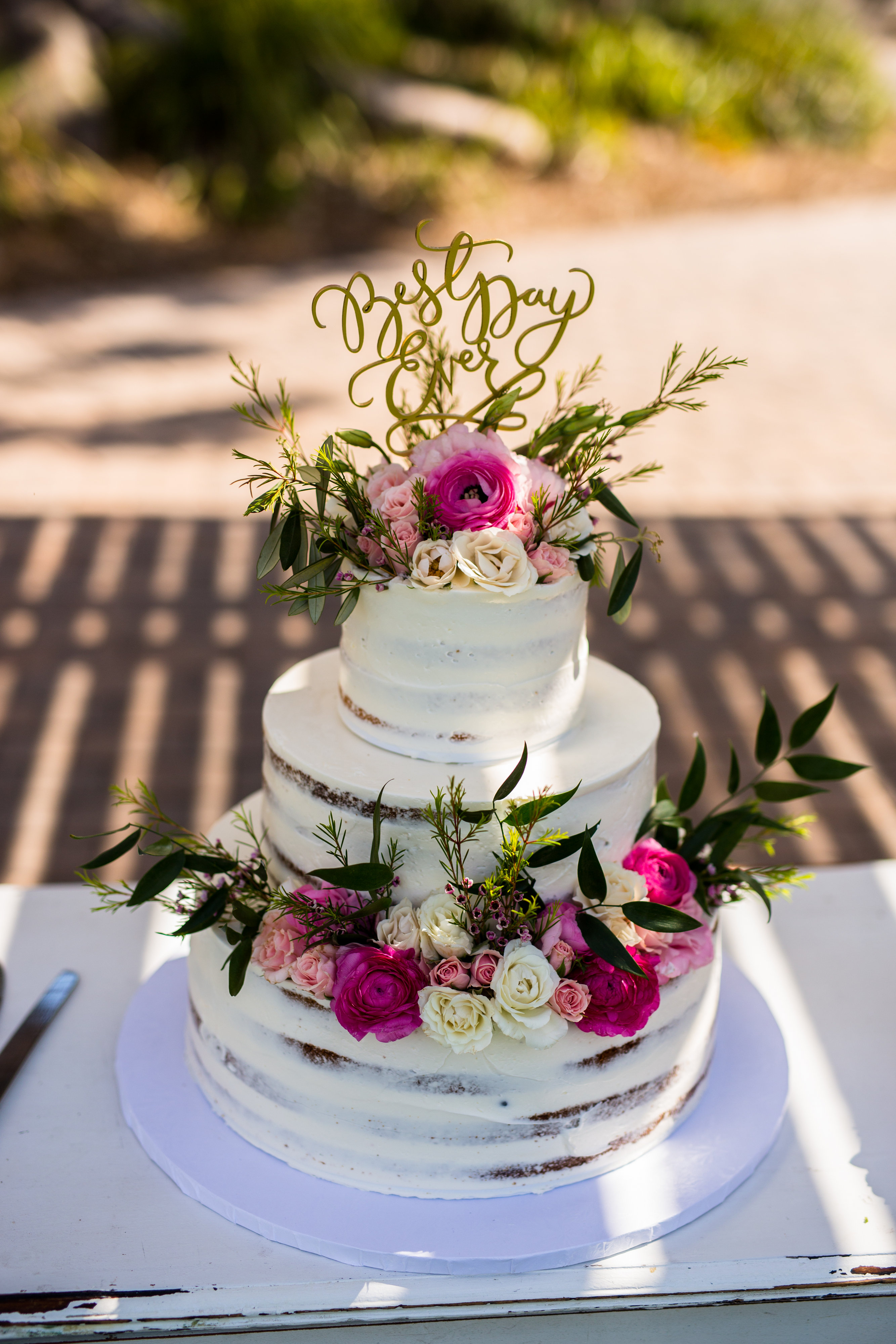 naked cake with pink and white flowers