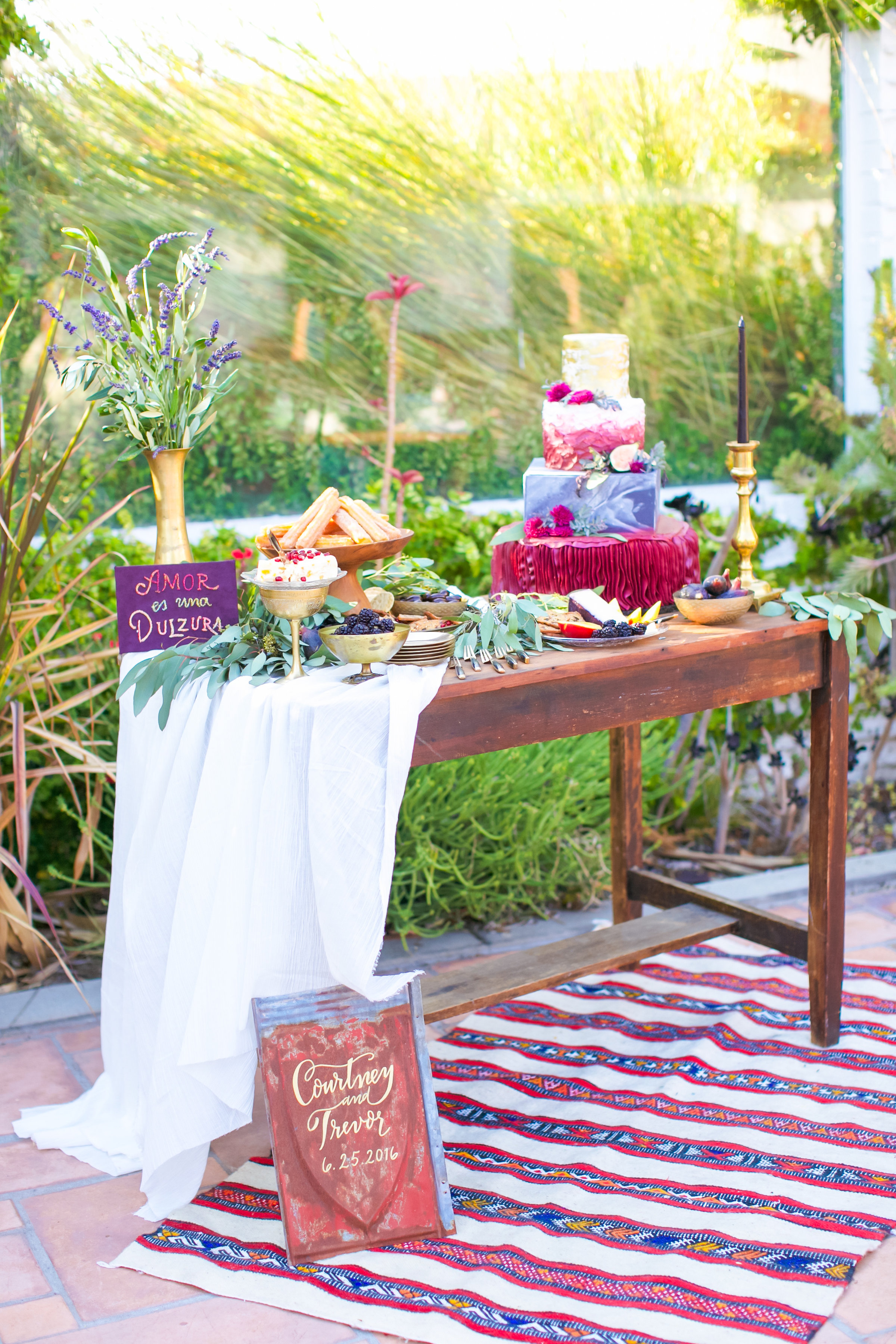 dessert table with churro bar and colorful cake