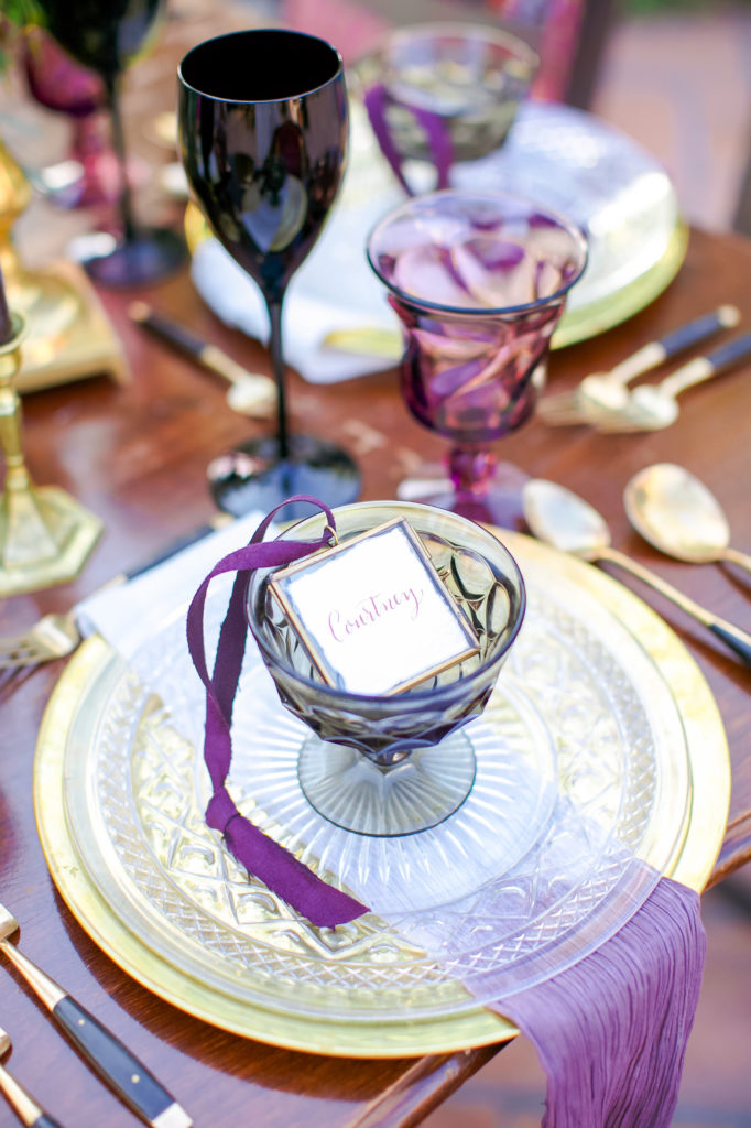 escort cards with gold chargers and black wine glasses