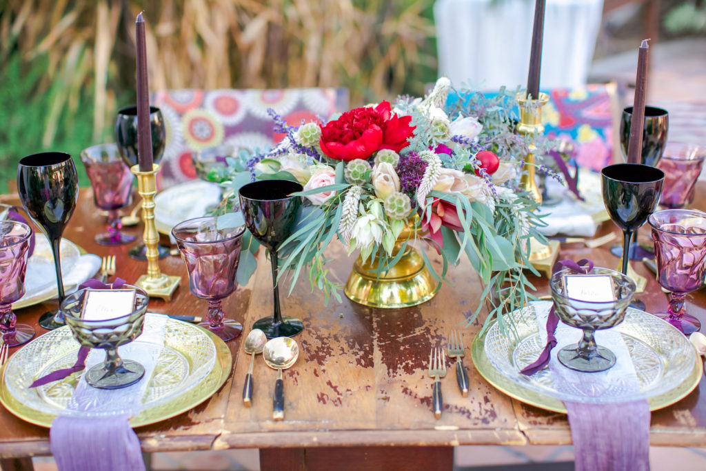 black wine glasses and colorful table decorations and florals