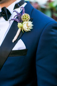 navy suit with lavender boutonniere