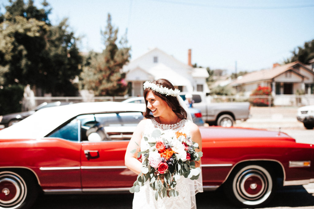 bride with bright bouquet and red convertible