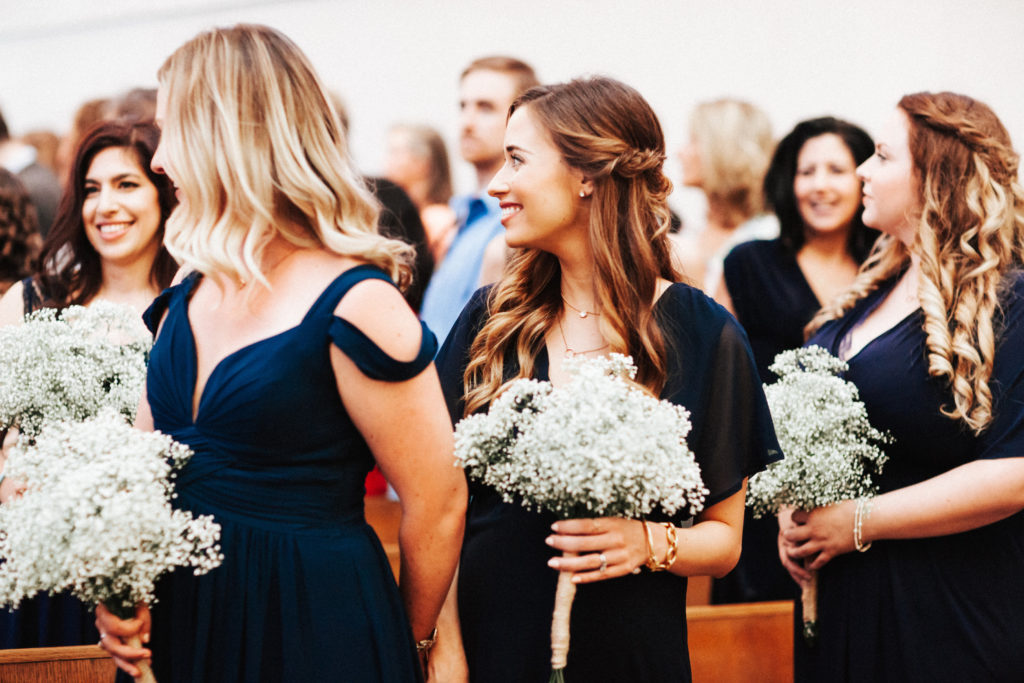 bridesmaids in navy with baby's breath bouquet