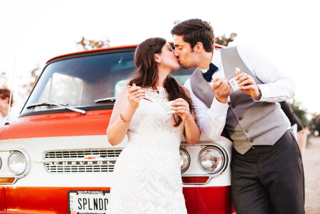 bride and groom kiss in from of Jeni's Ice cream truck