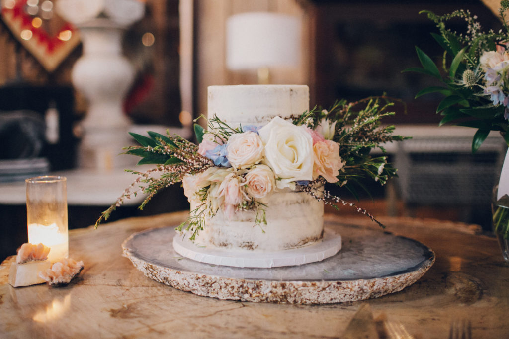 naked wedding cake with pink and blue flowers