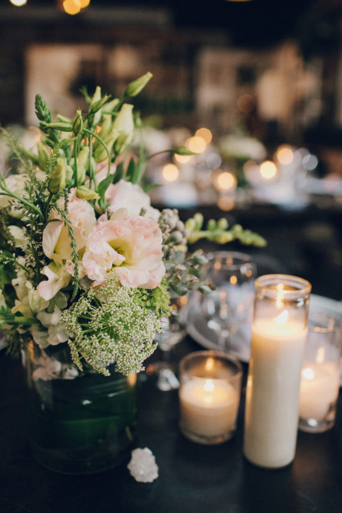 pink and blue flowers with tall candle at wedding in los angeles