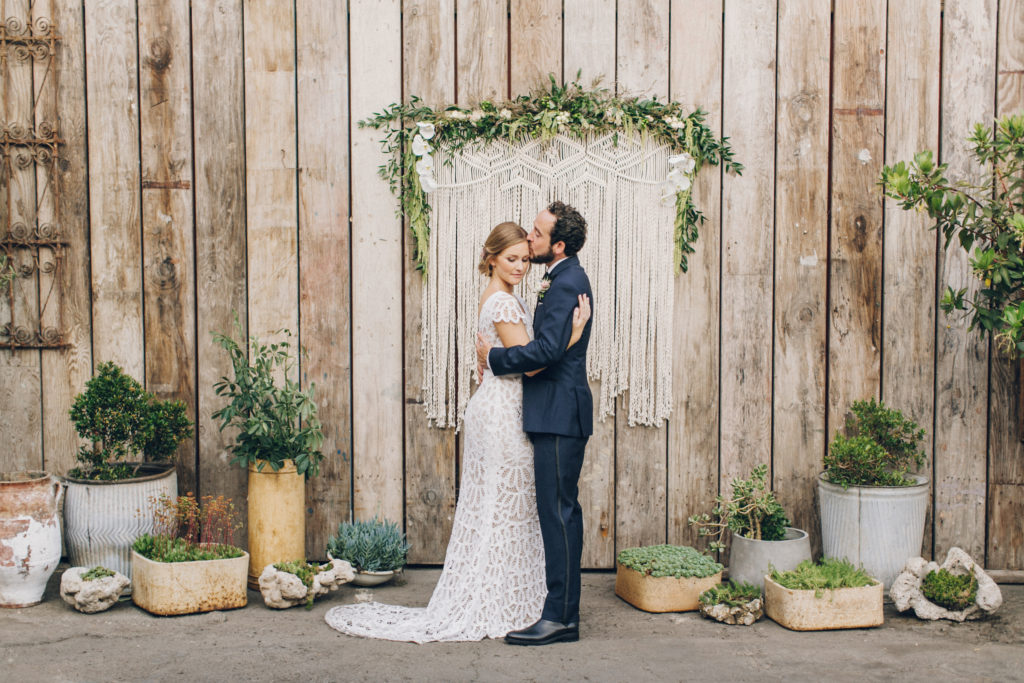ceremony with wooden wall and macrame backdrop lot's of plants and greenery big daddy's antiques