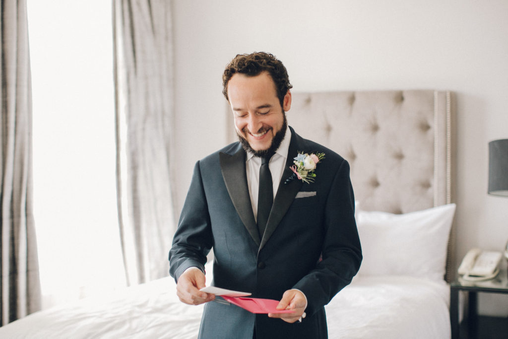 groom with tux opening letter