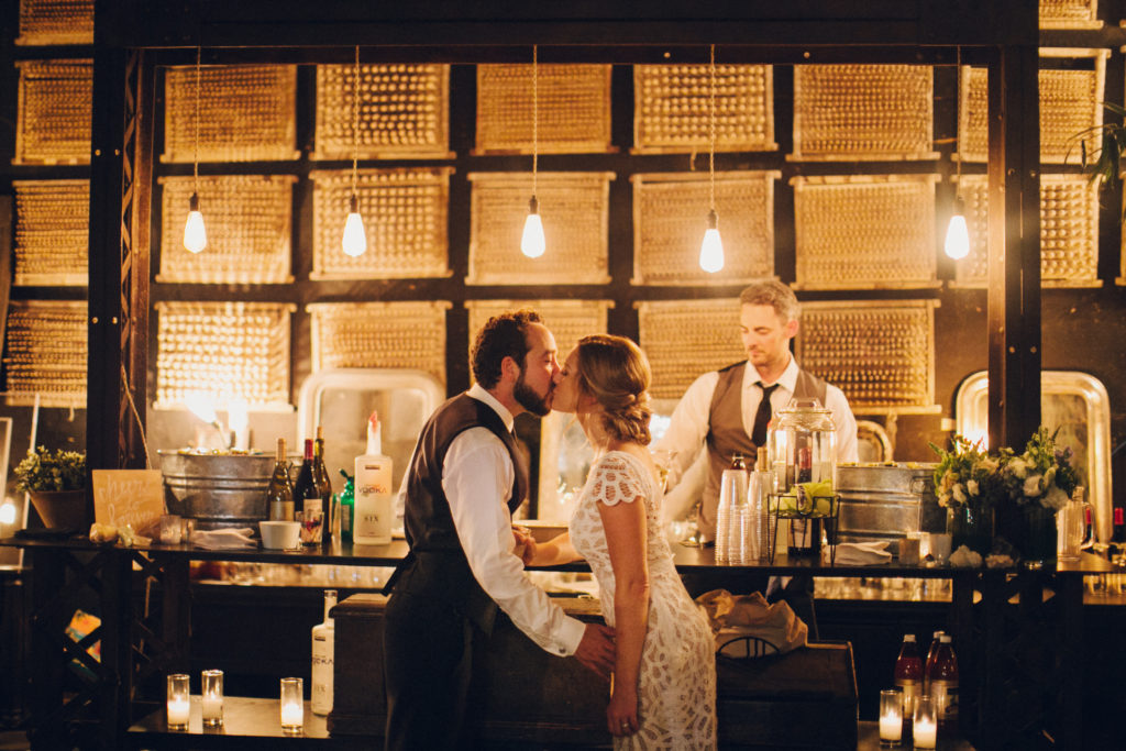 bride and groom kiss under edison lights by bar