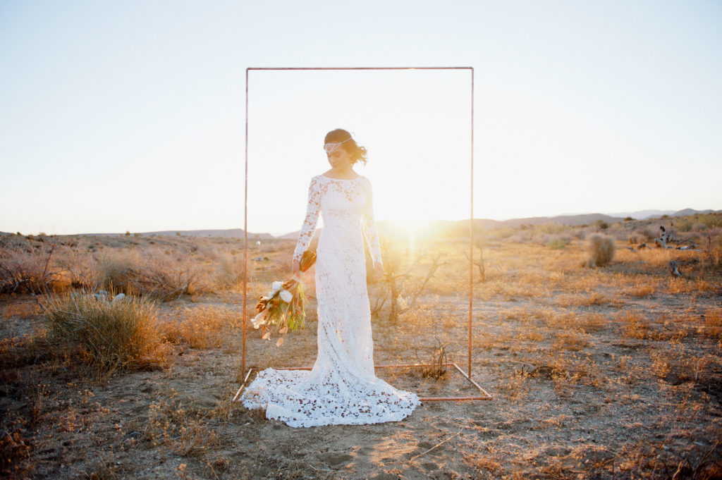 desert bride with lace dress and simple copper wedding arch joshua tree