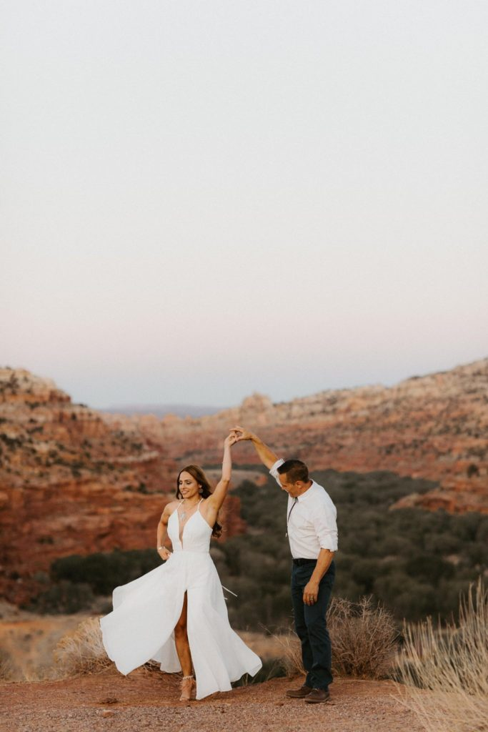 Bride twirls in dress with deep v neck with the red rocks of Escalante Utah behind them. Intimate wedding at Kiva Koffee House