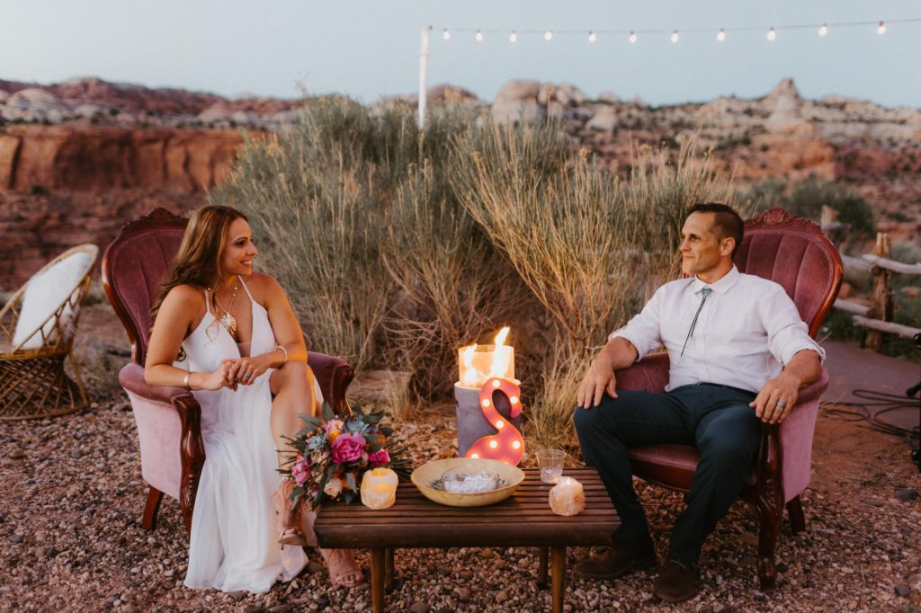 Bride and groom sitting outside the Kiva Koffeehouse on cute chairs they brought in as part of the wedding decor