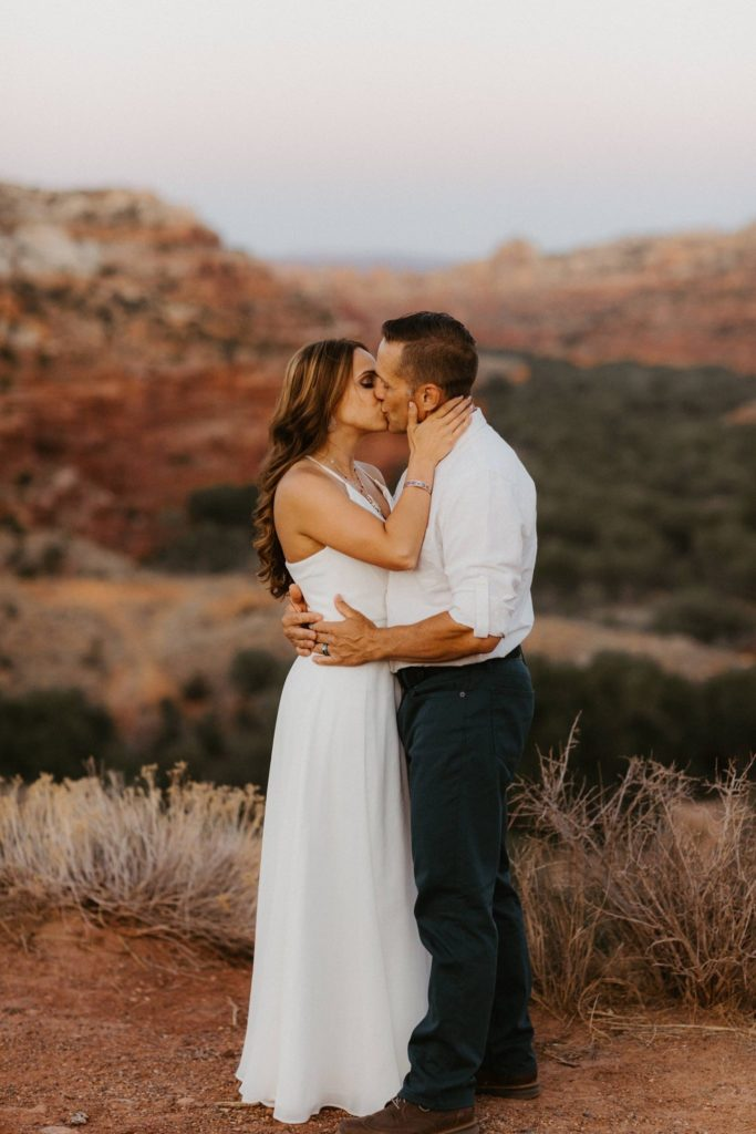 Bride and groom kiss with the red rocks of Escalante Utah behind them. Intimate wedding at Kiva Koffee house
