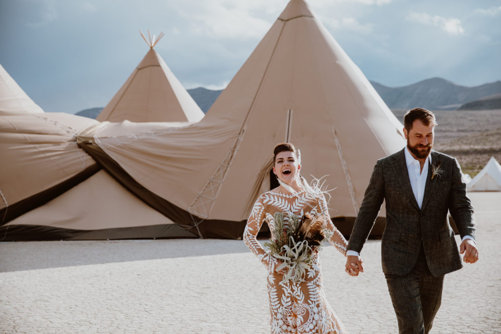 Bride in Rue de Seine gown with bouquet with feathers walking down the aisle in front of teepee. Burning man wedding on the playa