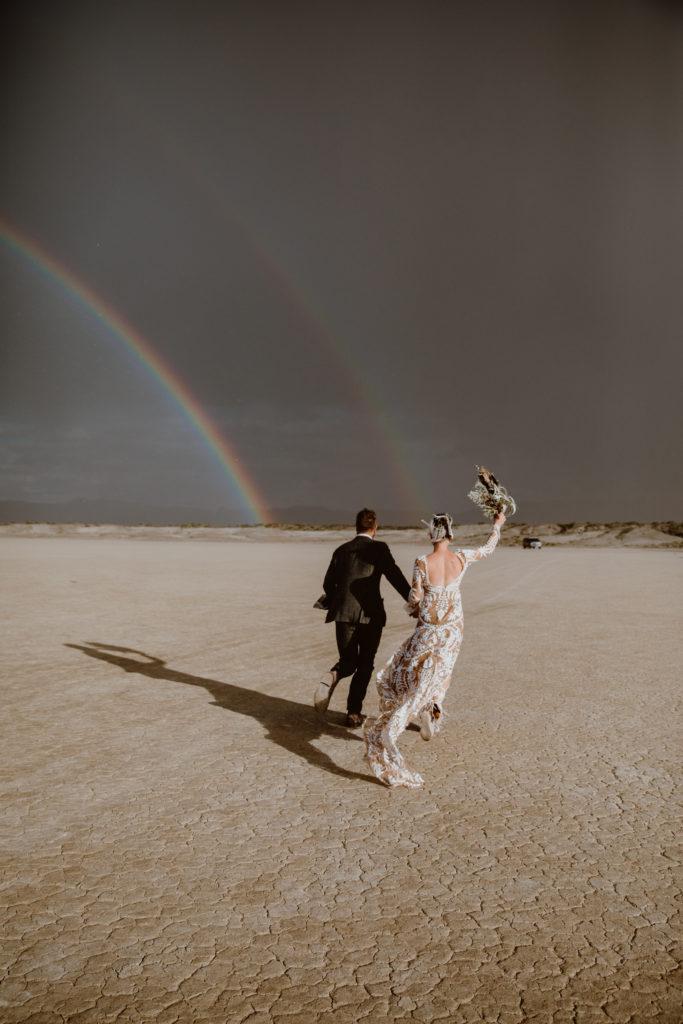 Bride and groom running on The Playa in Black rock desert under a double rainbow after burning man wedding