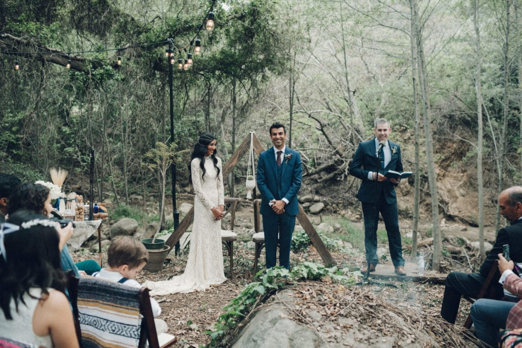 bohemian ceremony in the woods with triangle arch