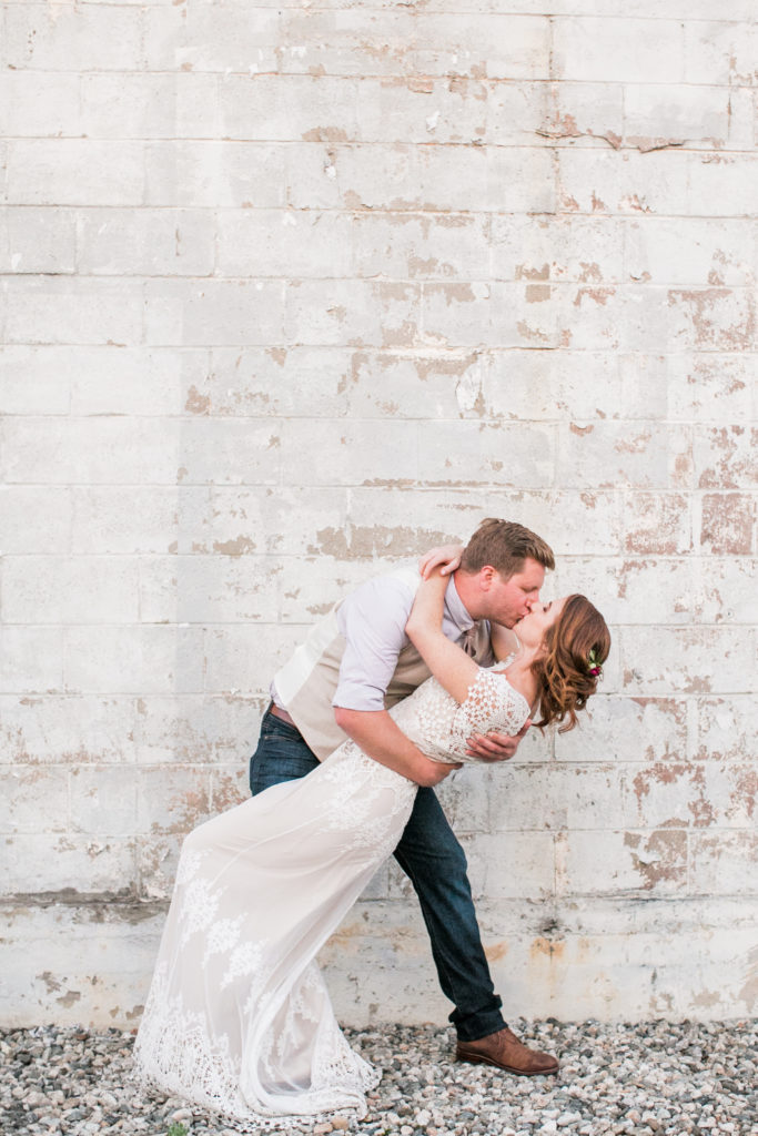 dip kiss bride and groom white brick wall
