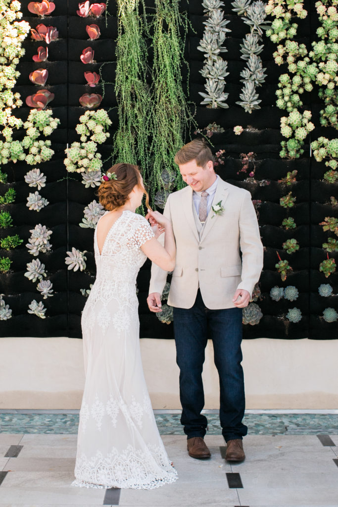 sweet first look in front of plant wall