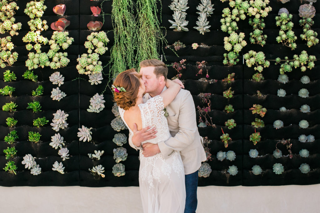 first kiss in front of plant wall