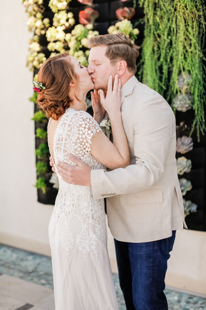 bride and groom kiss in front of succulent wall