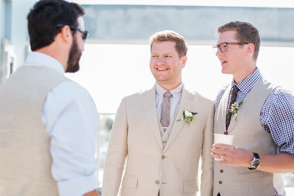 groom and groomsmen in light suits and grey ties