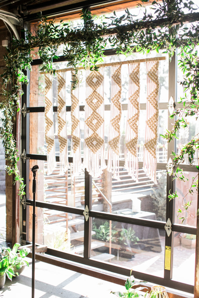macarame ceremony backdrop with greenery