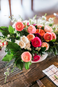 bright coral floral centerpieces on wooden table