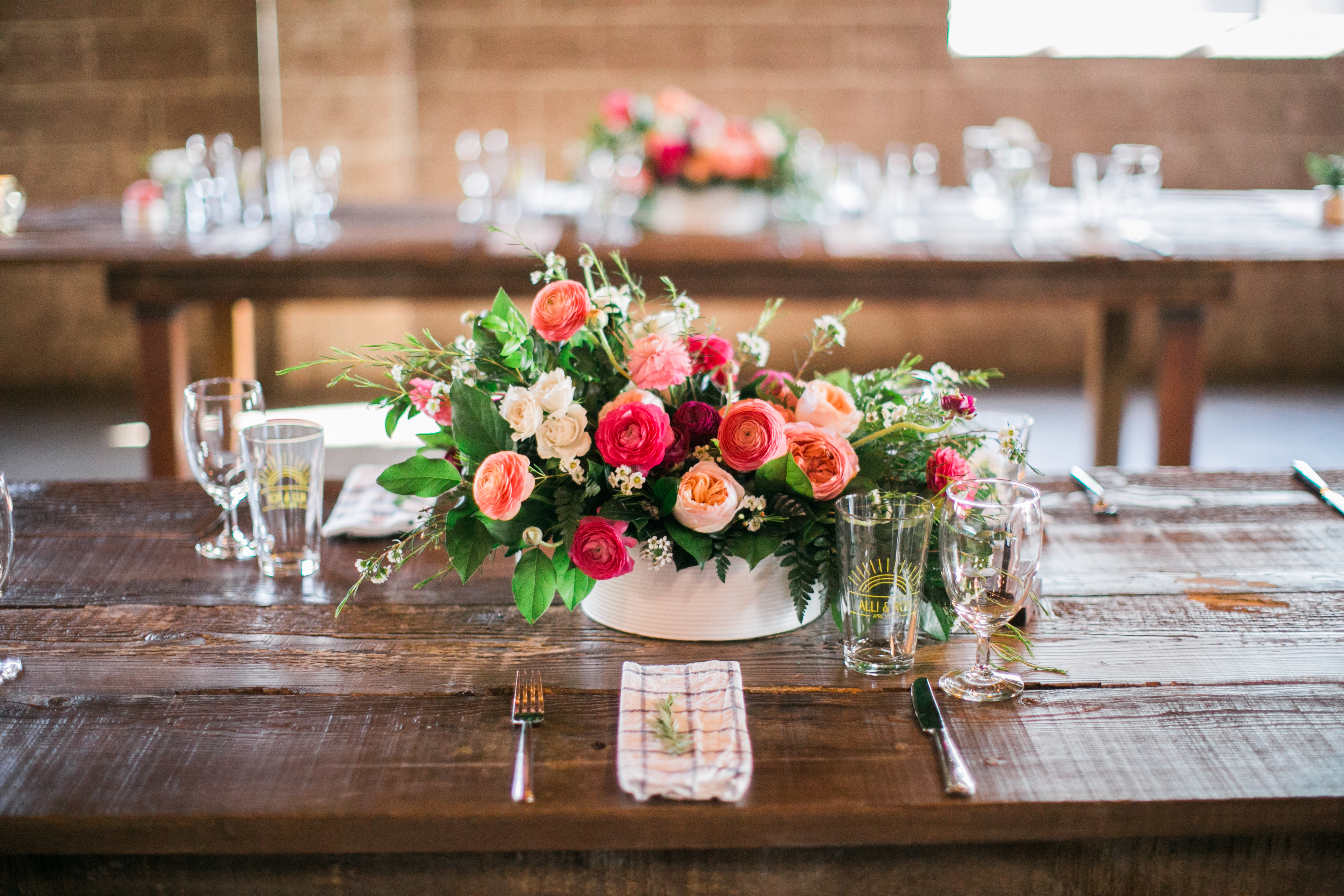 pink, coral and peach flowers on farm tables