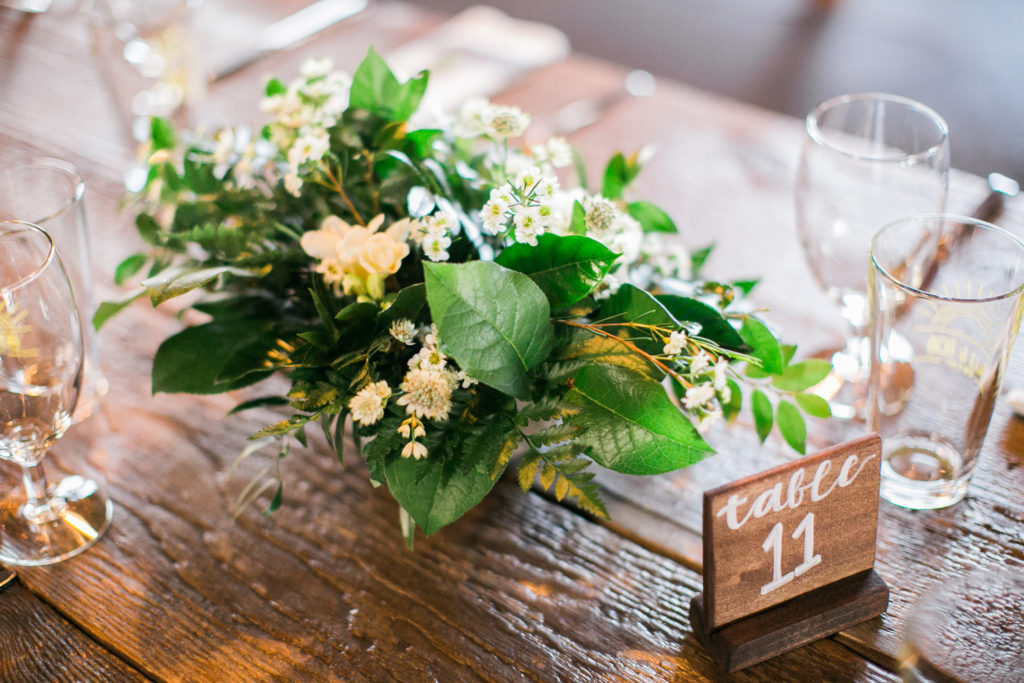 green and white floral centerpieces on farm table