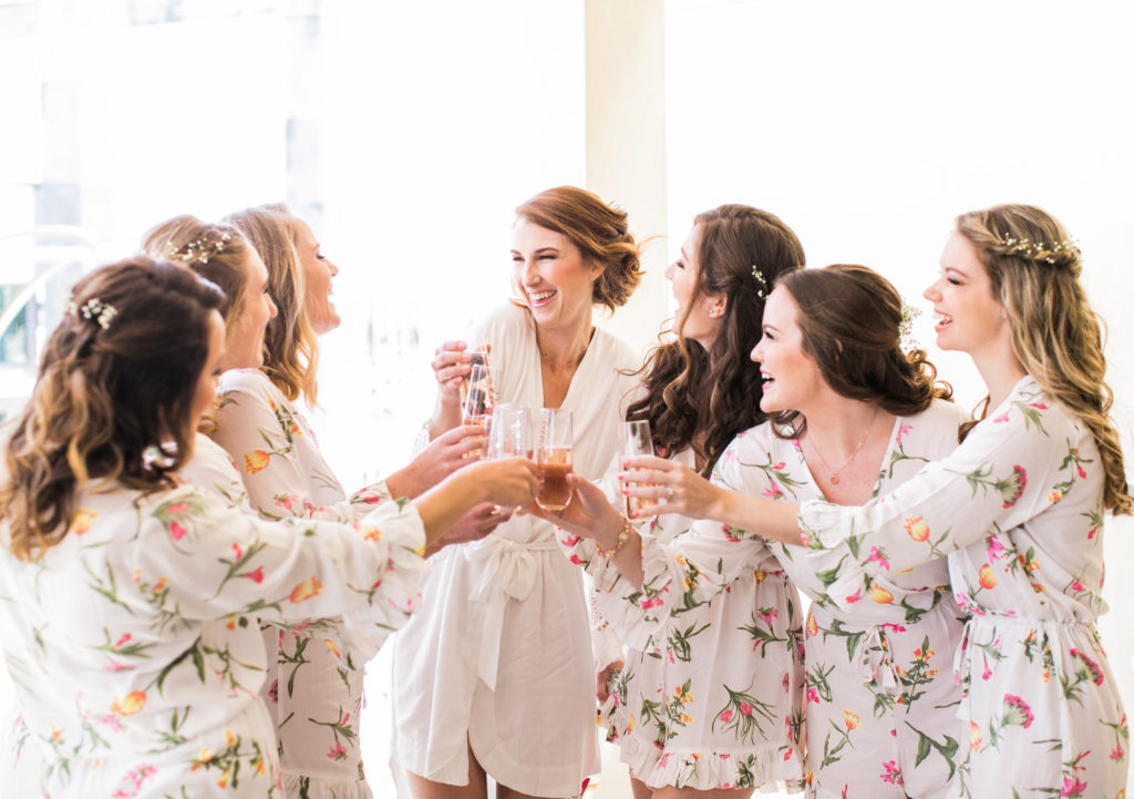 bride and bridesmaids cheers in rompers