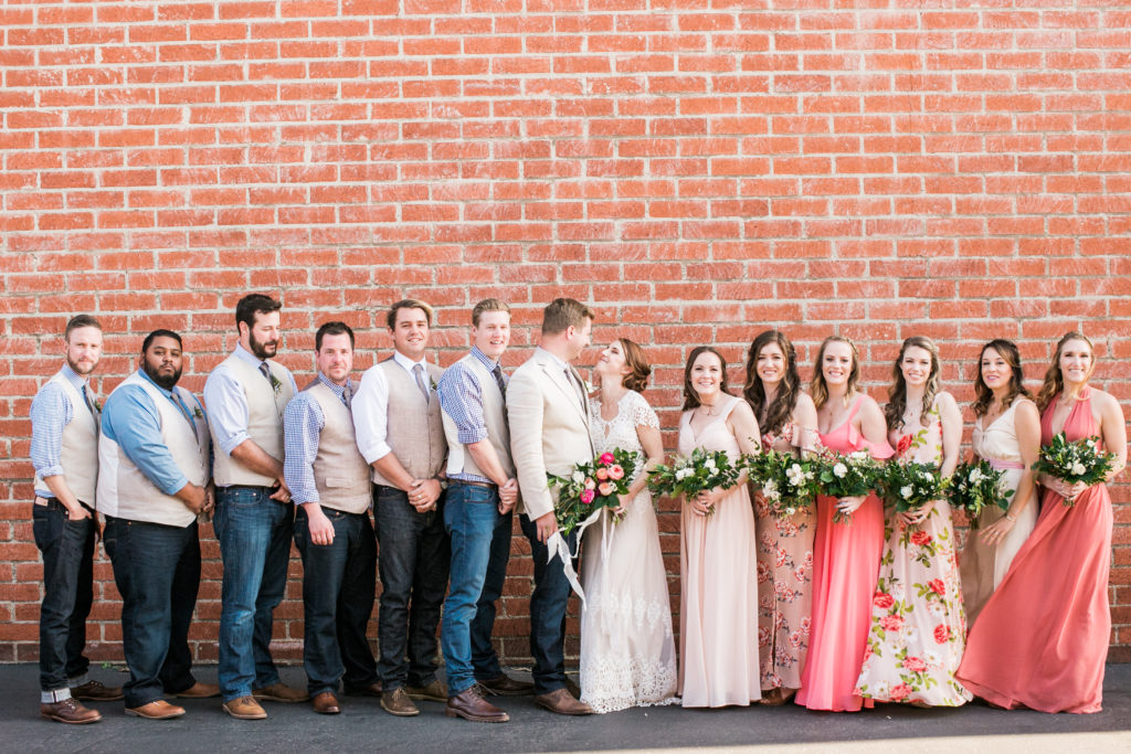 bridal party in front of brick wall