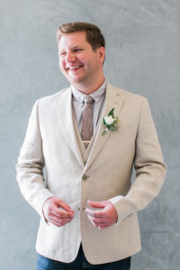 Groom with light suit, grey tie and white and green boutoniere