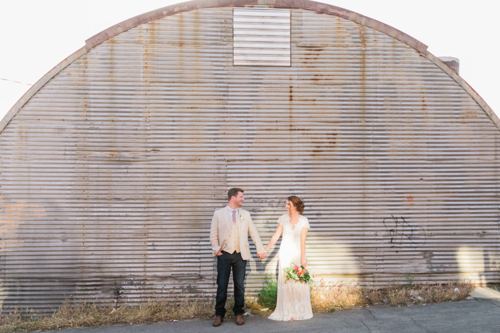 bride and groom in front of warehouse