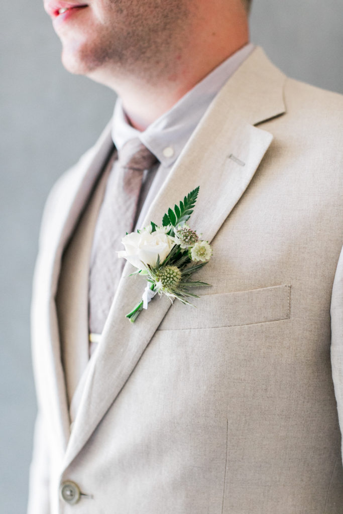 white and green boutonniere on light suit