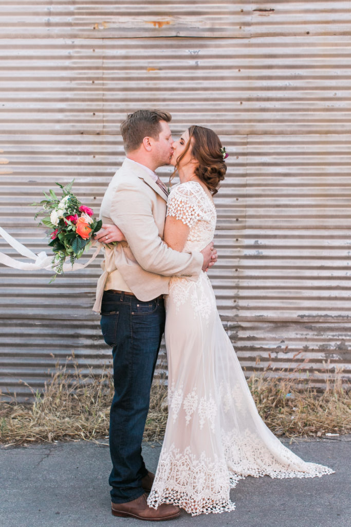 bride and groom kiss outside smoky hollow studios