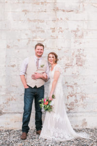 bride and groom in front of white brick wall