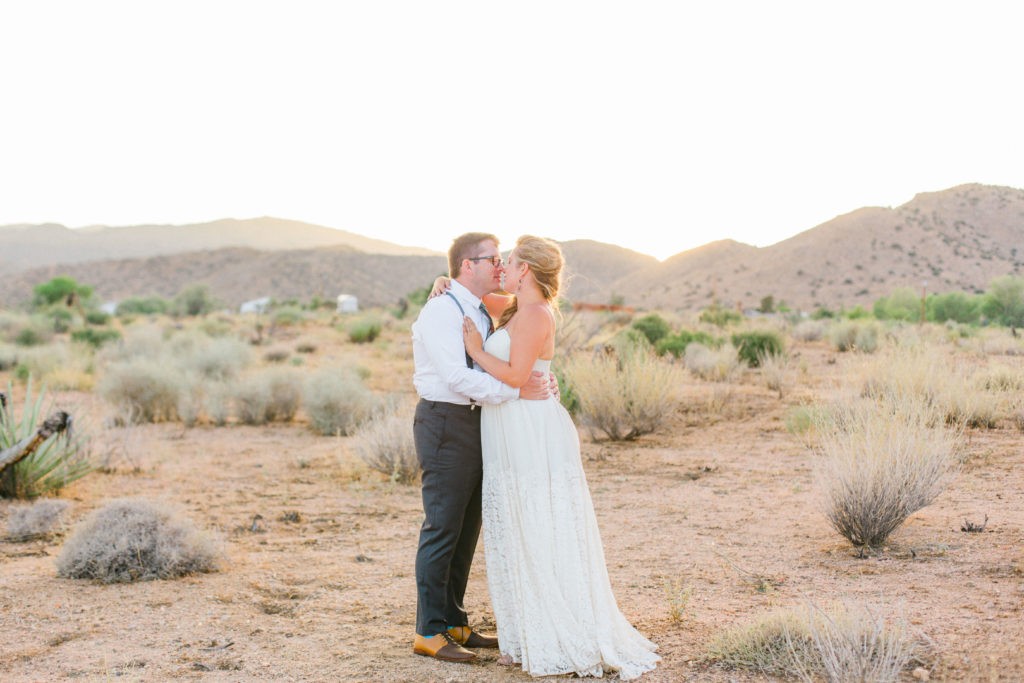 bride and groom kiss in the desert in joshua tree
