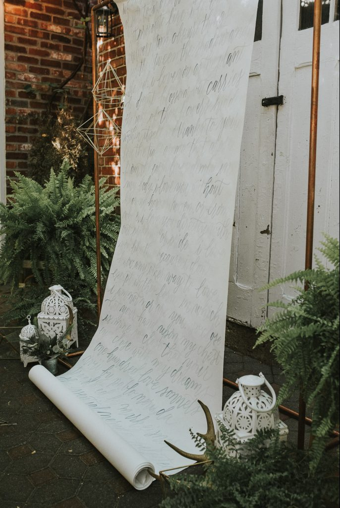 ceremony backdrop with vows written on scroll and ferms