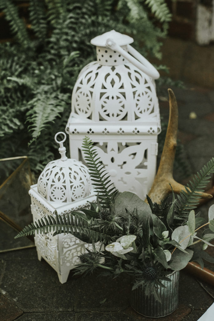 white lanterns and antlers with fern by ceremony arch