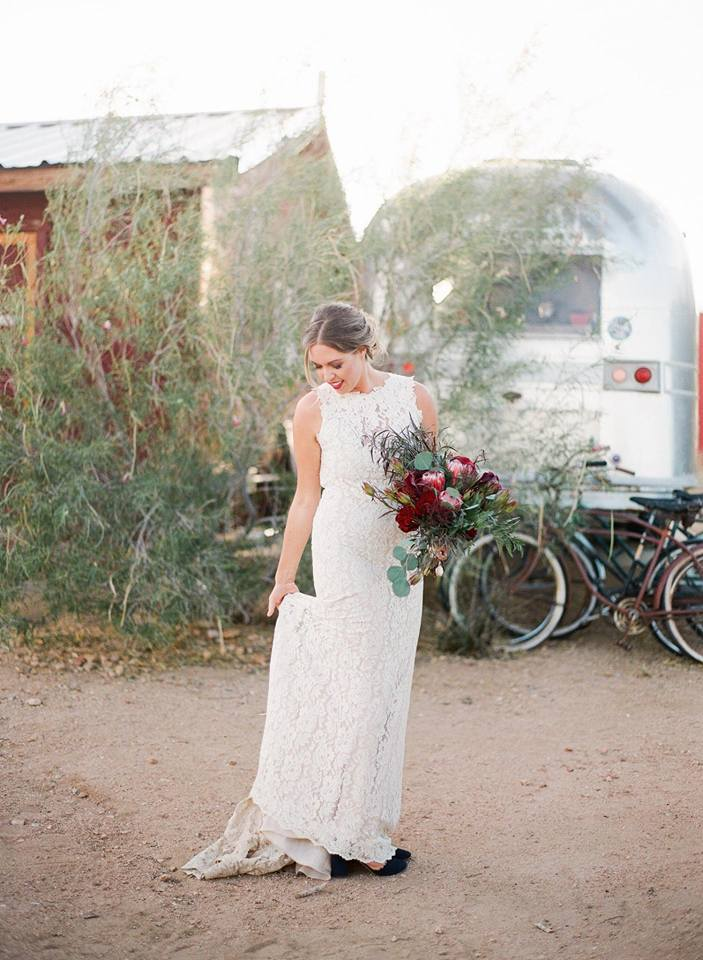 bride with bold lip in high next lace dress with dark floral bouquet desert wedding