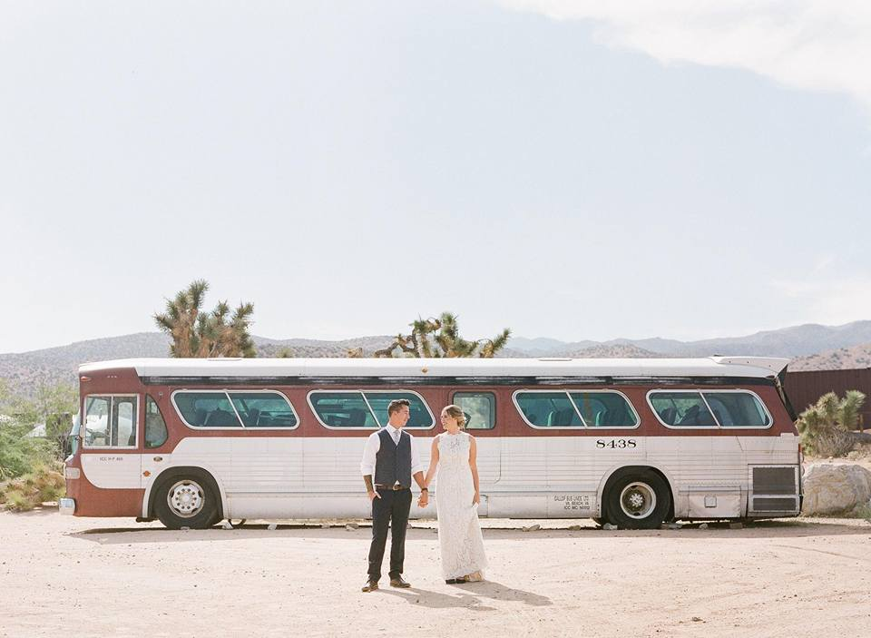 bride and groom at rimrock ranch in front of vintage bus