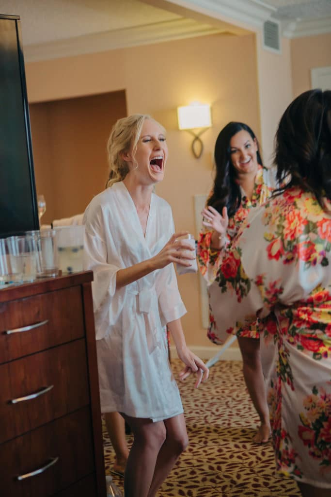 bride laughing and bridesmaids in cute floral robes