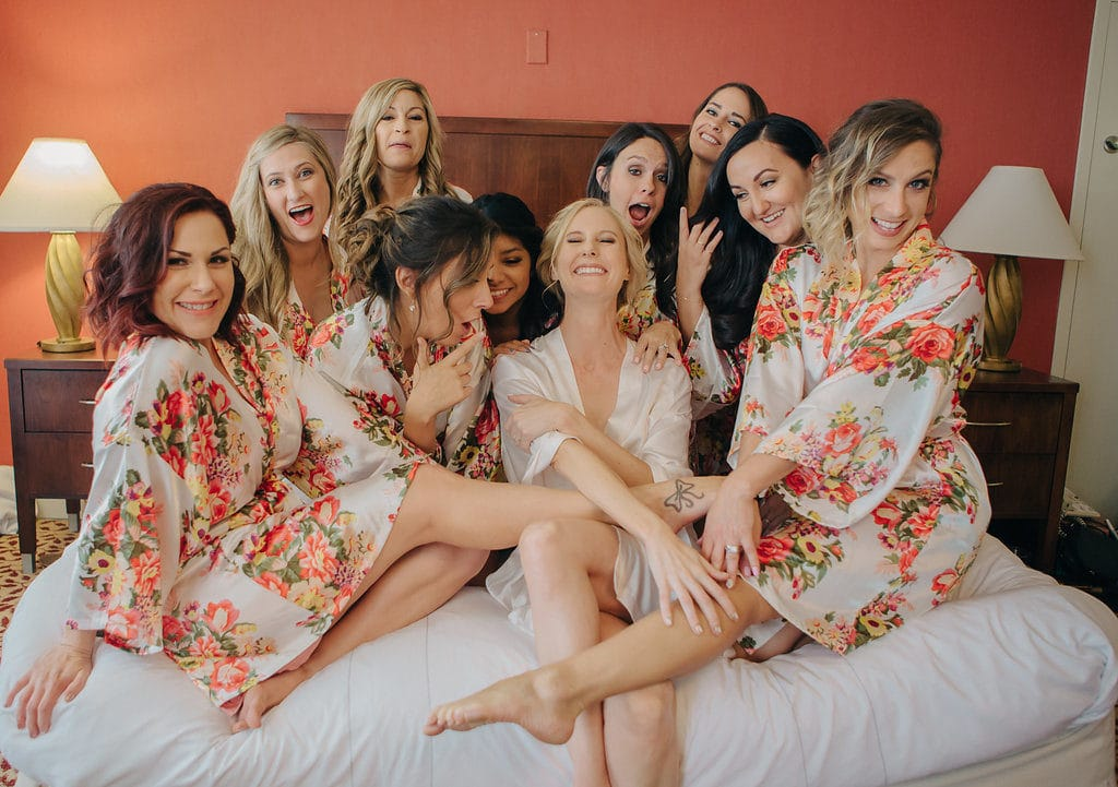 bridesmaids laughing in cute floral robes on bed