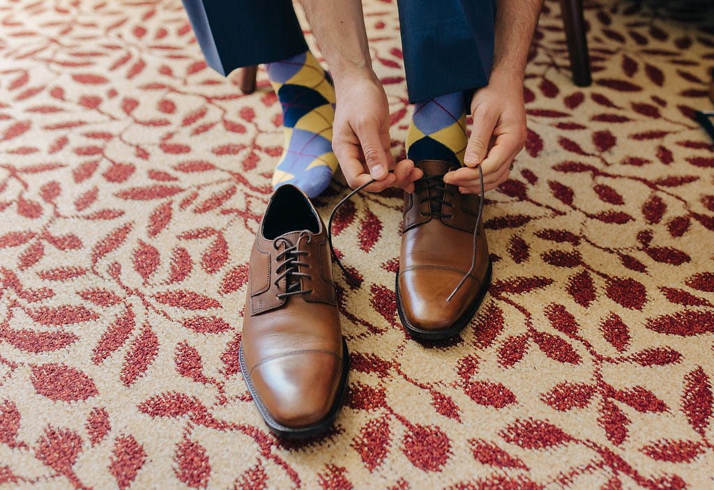 groom putting brown shoes on and argyle socks