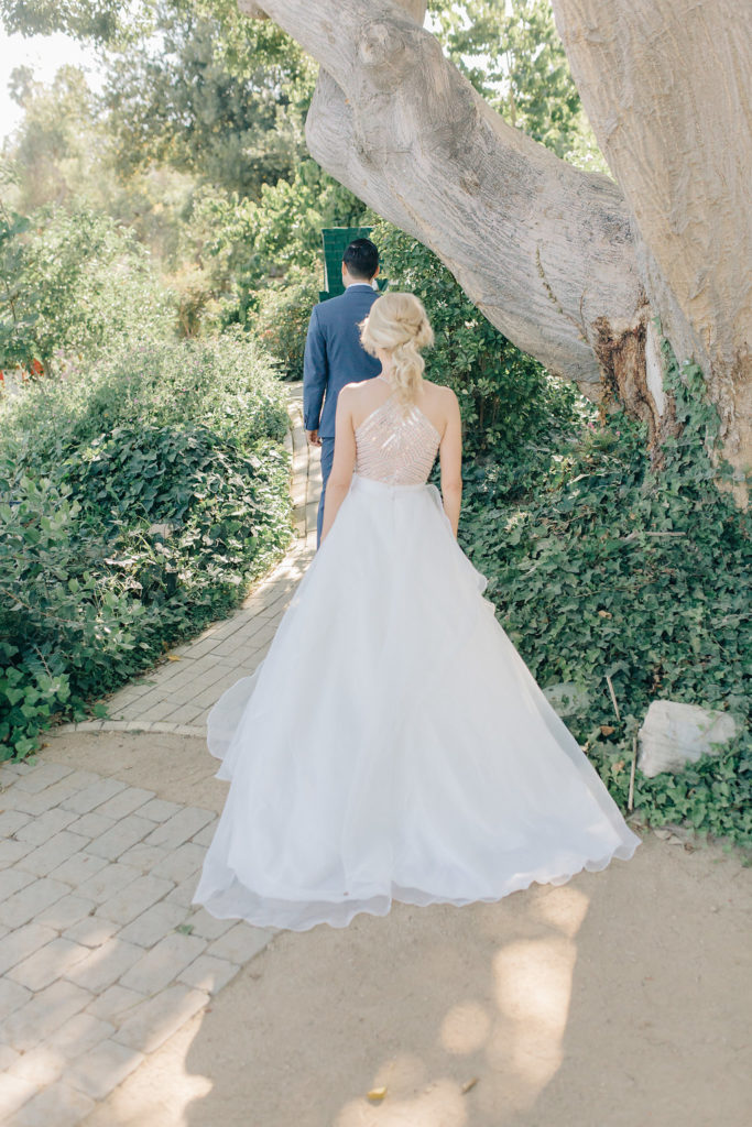 bride in beautiful fairytale gown in garden for first look