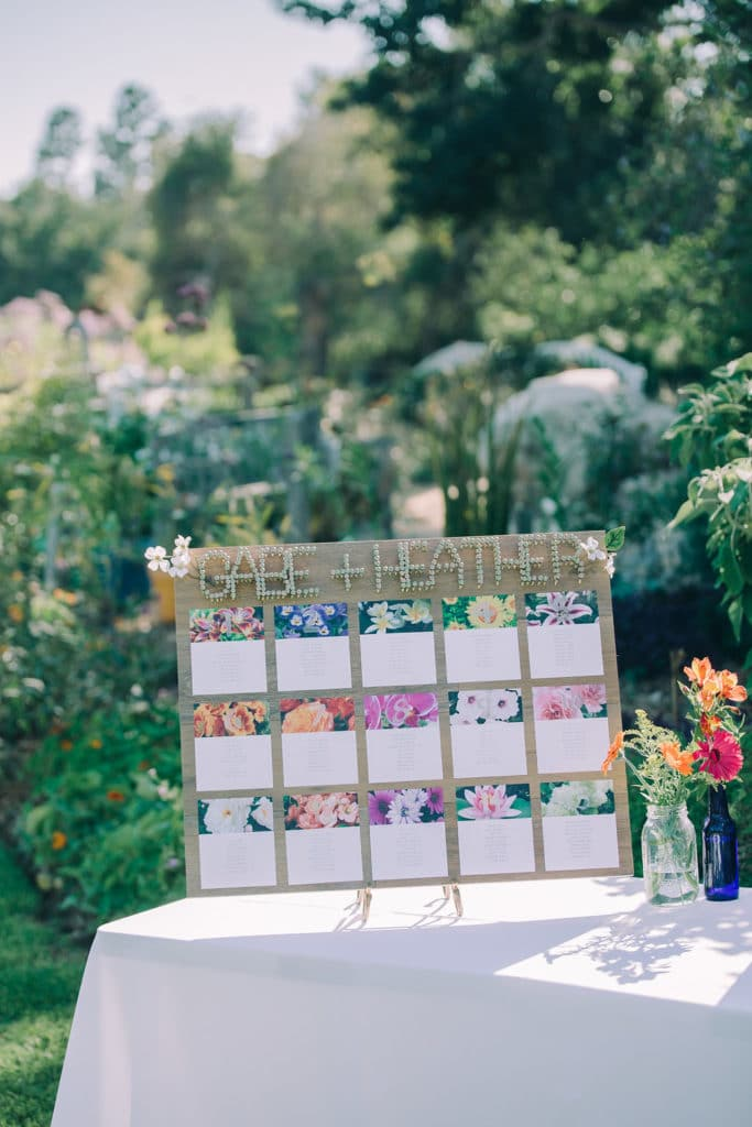 wooden seating chart with flowers and screws