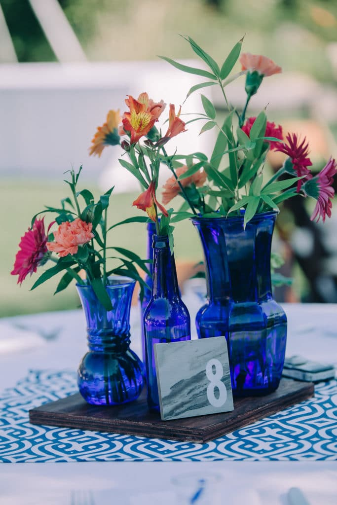 bright blue bottles and flowers with marble table number